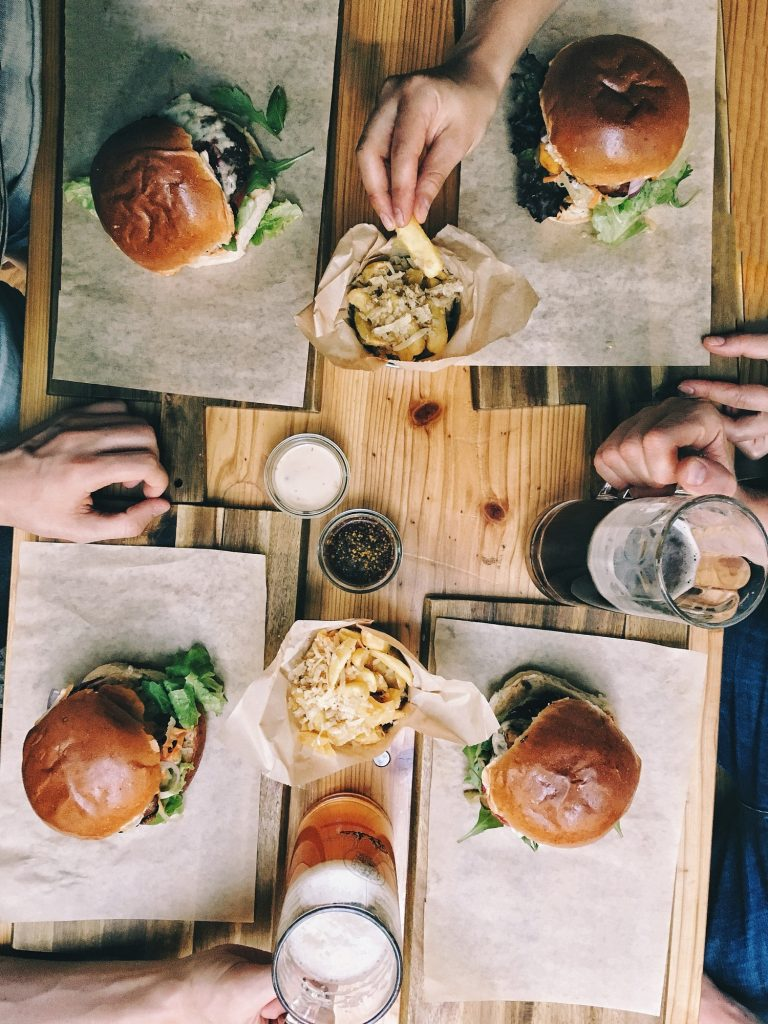 Top view of a group of friends eating burgers and fries with beer